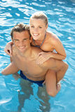 Pares jovenes que se divierten en piscina Fotos de archivo libres de regalías