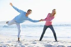 Pares jovenes que se divierten en Sandy Beach On Holiday Imágenes de archivo libres de regalías