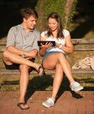 Pares jovenes que se divierten en un banco en parque mientras que socializa el ove Foto de archivo libre de regalías
