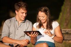 Pares jovenes que se divierten en un banco en parque mientras que socializa el ove Fotografía de archivo libre de regalías