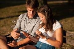Pares jovenes que se divierten en un banco en parque mientras que socializa el ove Fotos de archivo