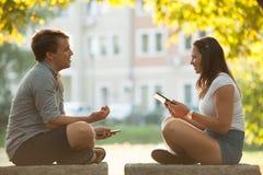 Pares jovenes que se divierten en un banco en parque mientras que socializa el ove Imágenes de archivo libres de regalías