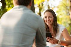 Pares jovenes que se divierten en un banco en parque mientras que socializa el ove Foto de archivo