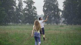Pares jovenes que se divierten en un claro del bosque, lanzando una cometa almacen de metraje de vídeo