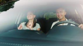 Pares jovenes que se divierten en un coche La diversión, canta y baila El parabrisas refleja árboles y las nubes al conducir un c metrajes
