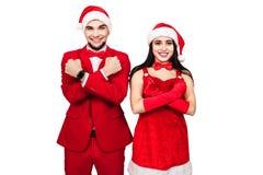 Pares jovenes que se divierten en un partido del tema de la Navidad hombre joven y mujer en trajes rojos con los sombreros de Pap fotos de archivo