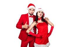 Pares jovenes que se divierten en un partido del tema de la Navidad hombre joven y mujer en trajes rojos con los sombreros de Pap foto de archivo libre de regalías