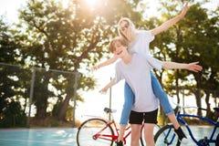 Pares jovenes que se divierten junto en parque con las bicicletas en fondo Muchacho alegre que juega con la muchacha hermosa aden Imágenes de archivo libres de regalías