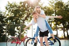Pares jovenes que se divierten junto en parque con las bicicletas en fondo Muchacho alegre que juega con la muchacha hermosa aden Imagen de archivo