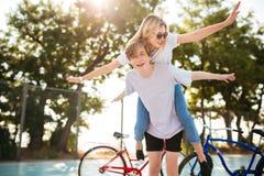 Pares jovenes que se divierten junto en parque con las bicicletas en fondo Muchacho sonriente que juega con la muchacha hermosa a Foto de archivo libre de regalías