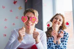 Pares jovenes que se divierten junto, presentando con las piruletas Imagen de archivo libre de regalías