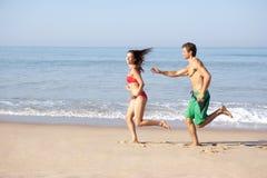 Pares jovenes que se ejecutan en la playa imágenes de archivo libres de regalías