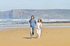Pares jovenes que se ejecutan en la playa Foto de archivo
