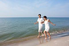 Pares jovenes que se ejecutan en una playa tropical Imagen de archivo libre de regalías