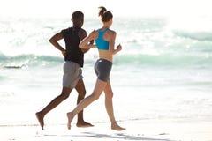 Pares jovenes que se ejecutan a lo largo de la playa fotos de archivo libres de regalías