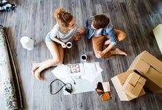 Pares jovenes que se mueven en la nueva casa, café de consumición foto de archivo