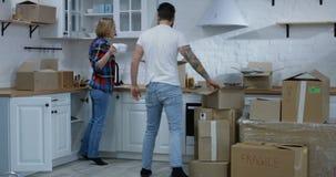 Pares jovenes que se mueven en su nuevo hogar almacen de video