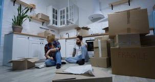 Pares jovenes que se mueven en su nuevo hogar almacen de metraje de vídeo