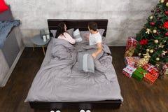 Pares jovenes que se preparan para dormir cerca del árbol de navidad con el presente Fotografía de archivo