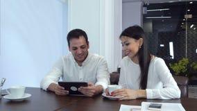 Pares jovenes que se ríen algo divertido en la tableta que espera su almuerzo almacen de video