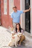 Pares jovenes que se reclinan con el perro en las escaleras Imágenes de archivo libres de regalías