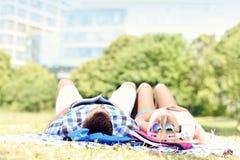 Pares jovenes que se reclinan en el parque Fotografía de archivo libre de regalías