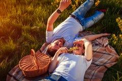 Pares jovenes que se relajan después teniendo comida campestre Mujer y hombre que mienten en hierba y que hablan en la puesta del Foto de archivo libre de regalías