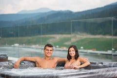 Pares jovenes que se relajan disfrutando del baño de burbujas de la tina caliente del Jacuzzi al aire libre en vacaciones románti Fotografía de archivo