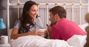 Pares jovenes que se relajan en cama con la bebida caliente Imagen de archivo
