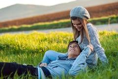 Pares jovenes que se relajan en campo de hierba verde. Fotos de archivo