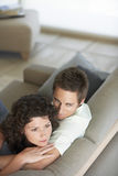 Pares jovenes que se relajan en el sofá Imagen de archivo