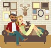 Pares jovenes que se relajan en el sofá Imagenes de archivo