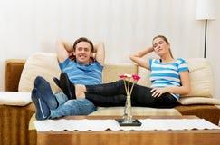 Pares jovenes que se relajan en el sofá Imágenes de archivo libres de regalías