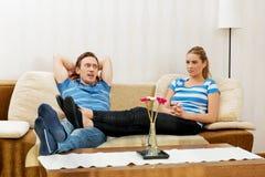 Pares jovenes que se relajan en el sofá Fotografía de archivo