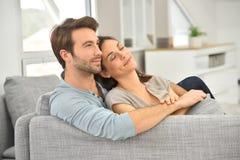 Pares jovenes que se relajan en el sofá y la reclinación Imagen de archivo libre de regalías