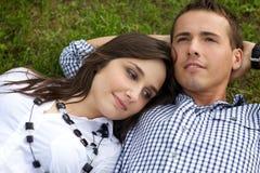 Pares jovenes que se relajan en hierba Fotos de archivo