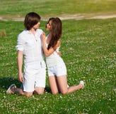 Pares jovenes que se relajan en la hierba Fotografía de archivo