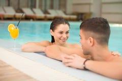 Pares jovenes que se relajan en la piscina Foto de archivo libre de regalías
