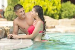 Pares jovenes que se relajan en la piscina Foto de archivo