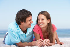 Pares jovenes que se relajan en la playa Imagen de archivo libre de regalías