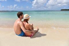 Pares jovenes que se relajan en la playa aislada Fotos de archivo