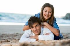 Pares jovenes que se relajan en la playa en la puesta del sol. Fotografía de archivo libre de regalías