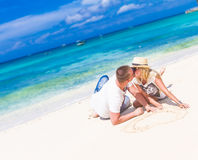 Pares jovenes que se relajan en la playa tropical de la arena en el cielo azul Fotos de archivo libres de regalías