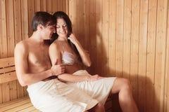 Pares jovenes que se relajan en la sauna Imágenes de archivo libres de regalías