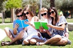 Pares jovenes que se relajan en libros del parque y de lectura Fotos de archivo libres de regalías