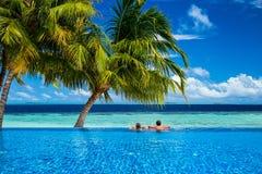 Pares jovenes que se relajan en piscina del infinito Foto de archivo libre de regalías