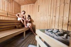 Pares jovenes que se relajan en sauna Foto de archivo libre de regalías