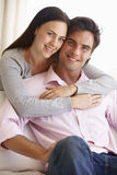 Pares jovenes que se relajan en Sofa Together At Home Fotografía de archivo