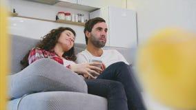 Pares jovenes que se relajan en su apartamento, mintiendo en el sofá y mirando la película almacen de metraje de vídeo