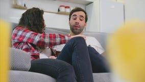 Pares jovenes que se relajan en su apartamento, mintiendo en el sofá y mirando la película metrajes